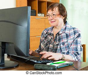 Ältere Frau, die mit Computern arbeitet.