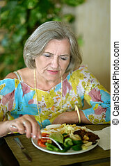 Ältere Frau isst Frühstück.