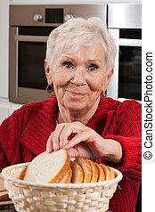 Ältere Frau nimmt Brot.