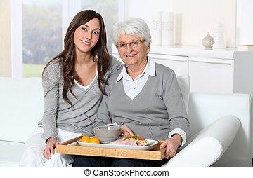 Ältere Frau und Hauspfleger sitzen im Sofa mit Lunchtablett.