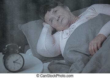 Ältere Frau versucht zu schlafen.