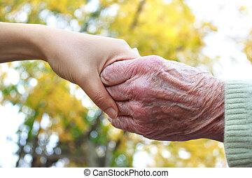 Ältere und junge Händchen halten.