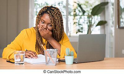Afrikanische Amerikanerin, die mit Laptop-Cover-Mund mit Hand geschockt mit Scham für Fehler, Ausdruck der Angst, Angst in Stille, Geheimkonzept.