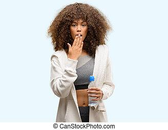 Afrikanische amerikanische Fitness-Frau mit Wasserflaschen bedeckt Mund mit Hand schockiert vor Scham aus Versehen, Ausdruck der Angst, Angst in Stille, Geheimkonzept.