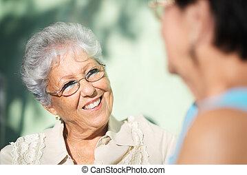 Alte Freunde, zwei glückliche Senioren, die im Park reden