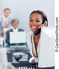 Animierte Geschäftsfrau am Telefon an ihrem Schreibtisch