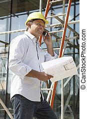 Architekt mit Plänen außerhalb des neuen Zuhauses, die über Handy reden