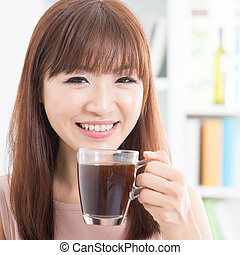 Asiatin, die Kaffee trinkt