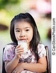 Asiatin trinkt Milch.