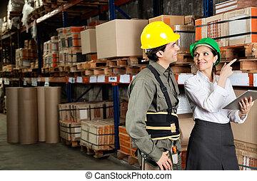 Aufseher mit Vorarbeitern, die auf Regale zeigen