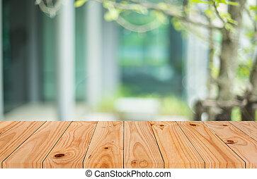 Ausgewählter Fokus leerer, brauner Holztisch und verschwommener Coffee Shop Hintergrund mit Bokeh-Bild, für die Produktpräsentation Montage.