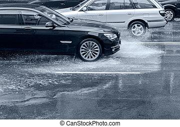 Auto fahren auf überfluteter Straße mit spritzwasser nach starkem Regen.