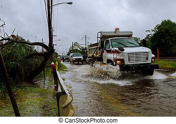 Autos fahren auf einer überschwemmten Straße während eines Hochwasserregens.