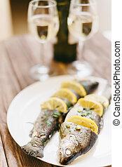 Backfischgericht und zwei Gläser Weißwein.