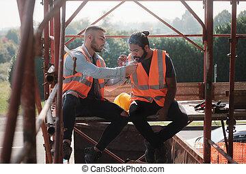 Bauarbeiter rauchen Zigaretten und reden über Pause