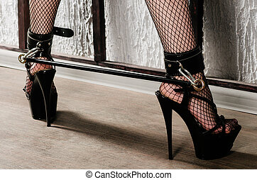 BDSM-Outfit für Erwachsene Sexspiele. Frauenbeine in schwarzen Strümpfen in hohen Absätzen sind mit Fesseln und Verbandsbändern verbunden
