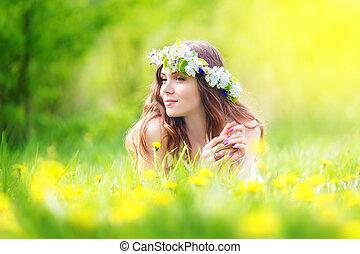 Bild einer hübschen Frau, die auf dem Dandelionsfeld liegt, glückliches, fröhliches Mädchen, das auf der Dandelionswiese ruht, Erholung im Frühling, Urlaub.