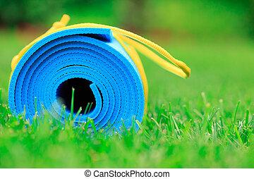 Blaue Yogamatte auf grünem Gras, Foto schließen, Fitnesskonzept.