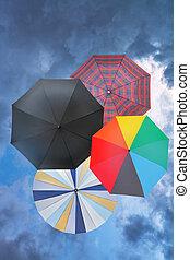 blaues, regnerisch, wolkenhimmel, vier, rgeöffnete, schirme