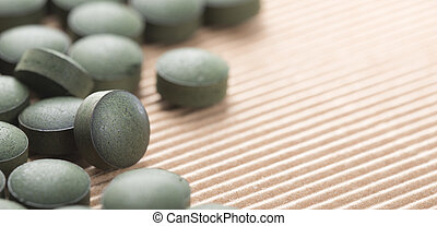 Blaugrüne Algen. Detail der handwerklichen Spirulina Tabletten über den natürlichen Hintergrund.
