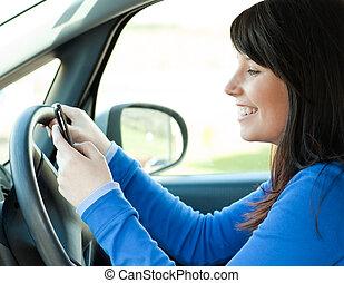 Brünette junge Frau schreibt eine Nachricht in ihrem Auto