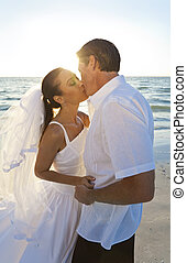 Braut- und Bräutigam heirateten Paar und küssten sich bei Sonnenuntergangs-Strand-Hochzeit