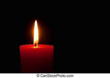 Brennende rote Kerze vor schwarzem Hintergrund