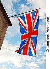 Britische Flagge weht im Wind. Im Hintergrund des blauen Himmels mit weißen Wolken