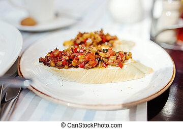 Bruschette, traditionelle italienische Vorspeise mit Tomaten und Auberginen auf dem Teller.