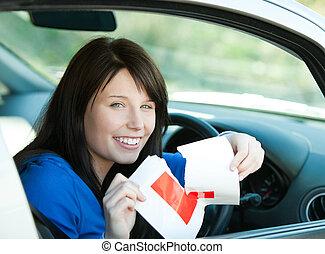 Charmante Brünette Teenie-Mädchen, die in ihrem Auto sitzt und ein L-sign reißt