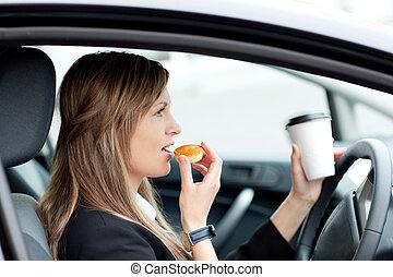 Charmante Geschäftsfrau, die isst und trinkt, während sie zur Arbeit fährt