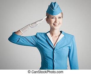 Charmante Stewardess in blauer Uniform auf grauem Hintergrund.