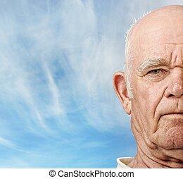 Das Gesicht eines älteren Mannes über dem blauen Himmel