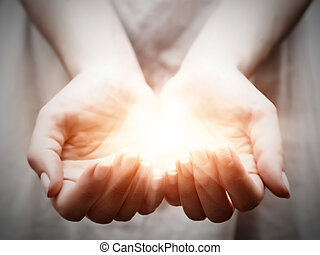 Das Licht in den Händen der jungen Frau. Teilen, geben, bieten, schützen