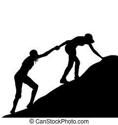 Das Mädchen hilft ihrem Freund, den letzten Teil des Berges hochzuklettern.