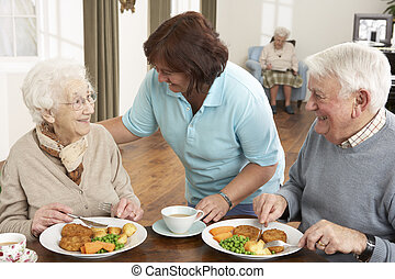Das Seniorenpaar wird mit Pfleger serviert.