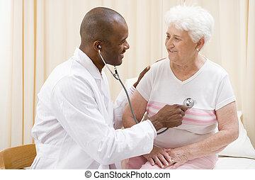 Der Doktor gibt eine Untersuchung mit Stethoskop an Frau im Untersuchungsraum Smi