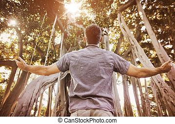Der entspannte Mann genießt die Sommerzeit in einem tropischen Wald.