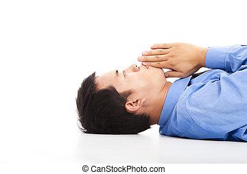Der Geschäftsmann liegt mit Beten auf dem Boden