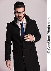 Der junge Geschäftsmann trägt einen langen, eleganten Mantel.