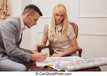 Der junge, gutaussehende Architekt diskutiert den Grundplan mit Kundensitz.