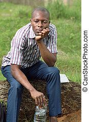 Der junge Mann sitzt auf einem Baumstamm.
