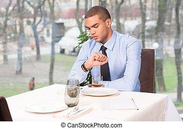 Der junge Mann wartet im Restaurant auf eine Frau. Eine Frau, die zu spät zum Date kommt und sich Uhren ansieht