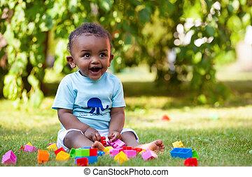 Der kleine afroamerikanische Junge, der im Gras spielt