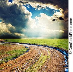 Der ländliche Weg unter dem dramatischen Himmel