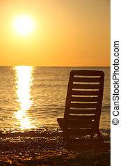 Der leere Stuhl steht seitwärts an der Küste am Abend während des Sonnenuntergangs