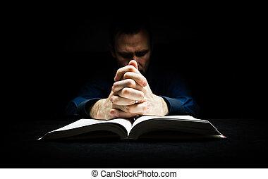 Der Mensch betet zu Gott mit seinen Händen auf einer Bibel.
