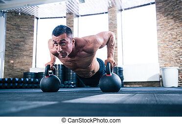 Der Muskelmann macht Liegestützen in der Turnhalle.
