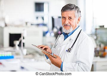 Der Senior Doktor benutzt seinen Tablet-Computer bei der Arbeit