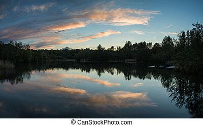 Der Sommer lebhafter Sonnenuntergang spiegelt sich in ruhigem Seewasser wider.
